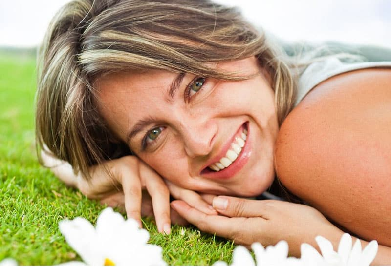sweet woman smiling lying down in the green grass with flowers nearby
