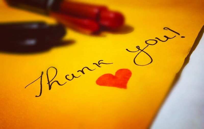 thank you heart text written in in yellow paper with ballpen place above the paper