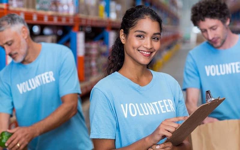 three persons volunteer in blue shirt with word volunteer