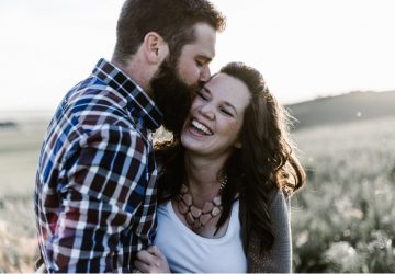 Man with beard kissing happy woman on a field