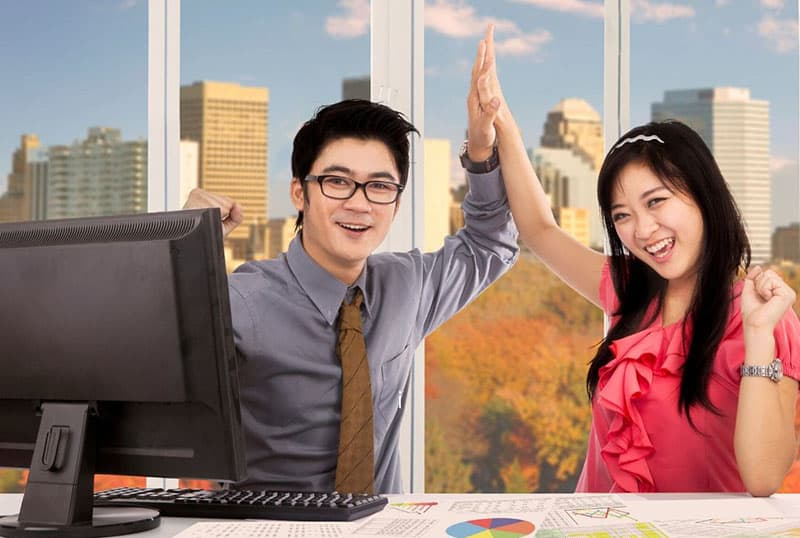 two asian workers celebrating by clapping their hands inside the office
