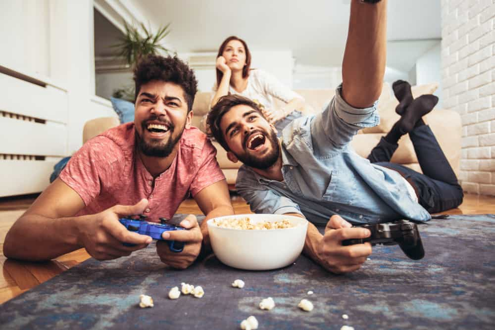 two guys playing video games with woman in background
