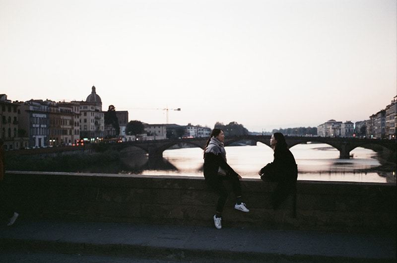 two person sitting on bridge while looking each other