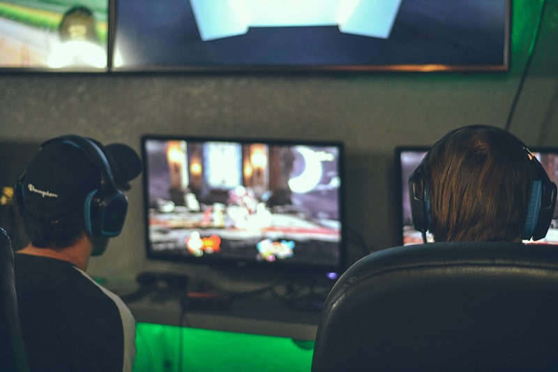 two persons playing game in front of monitors
