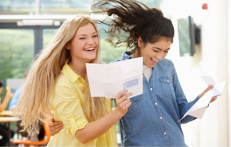 two women celebrating test results with good scores