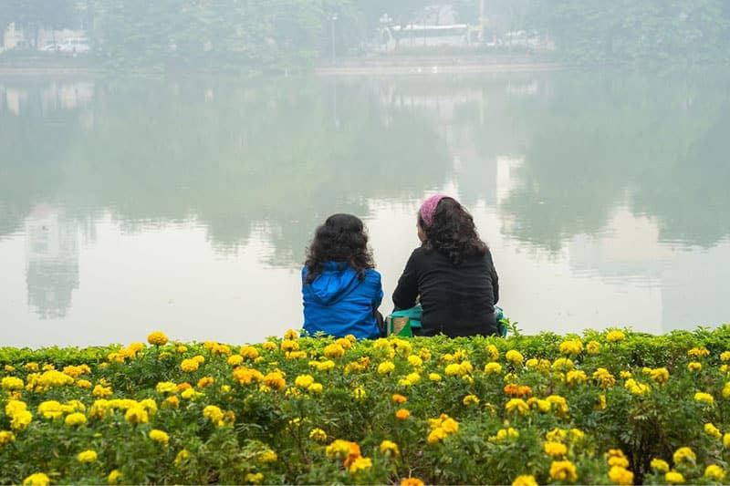 two women sitting and chatting on a lake of flowers