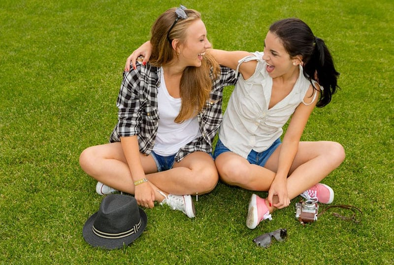 two women sitting on green grasses with arms around each other smiling