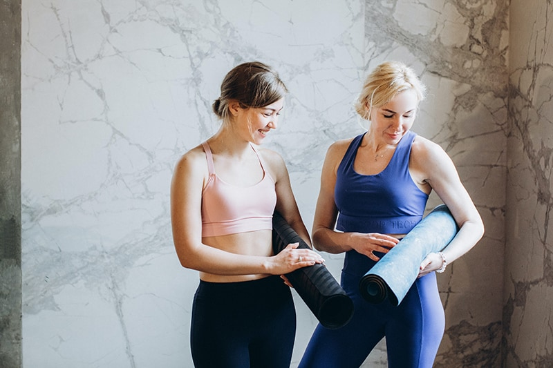 two women standing together while comparing yoga mats