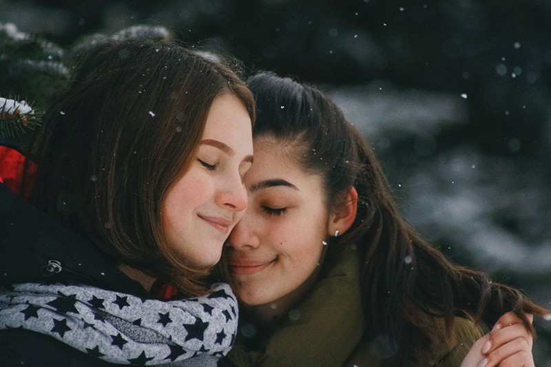 two women with closed eyes hugging each other