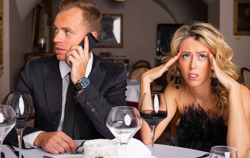 uncomfortable woman dating a guy busy with answering a call from the cellphone