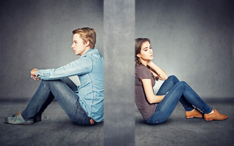 Grey wall between man and woman sitting on the floor