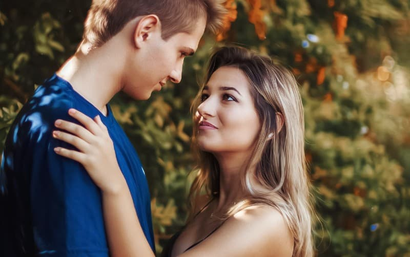 Woman and man face to face very close to each other outdoors