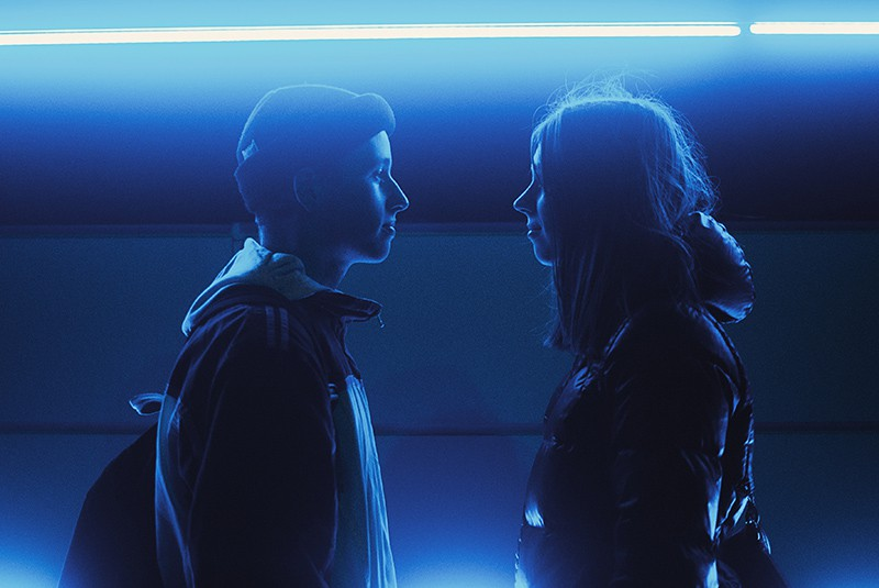 woman and man facing each other standing under blue lights