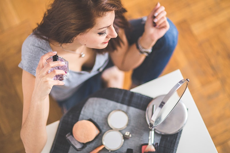woman applying perfume while sitting in front of the mirror