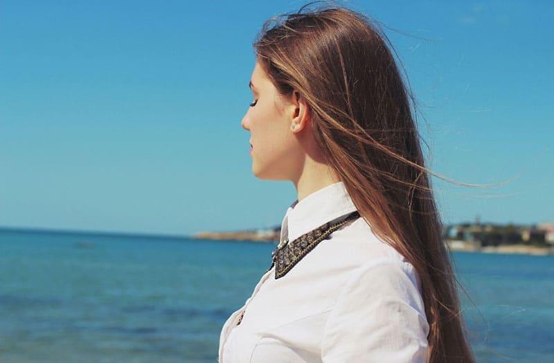 woman closing eyes thinking while facing the horizon above the sea
