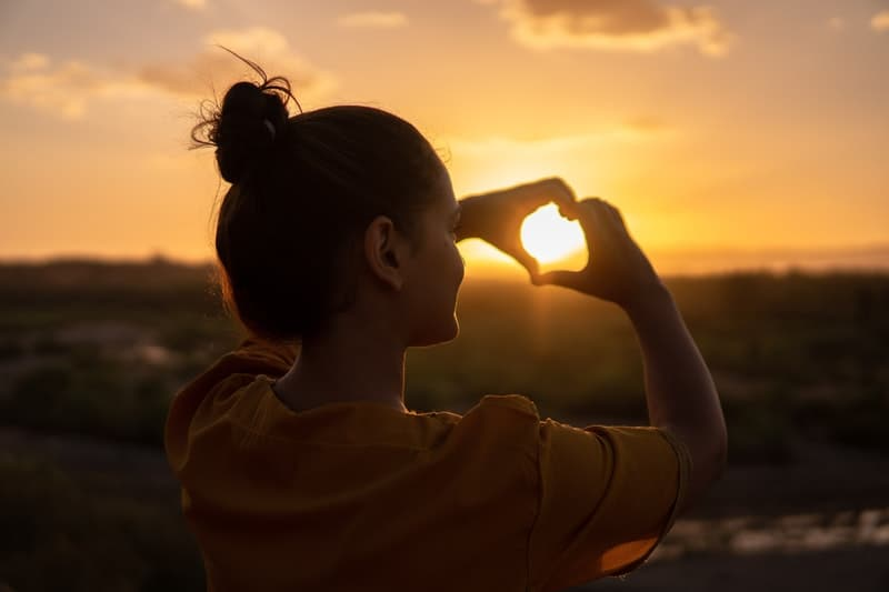 woman doing hand heart sign with the setting sun captured inside the hand sign