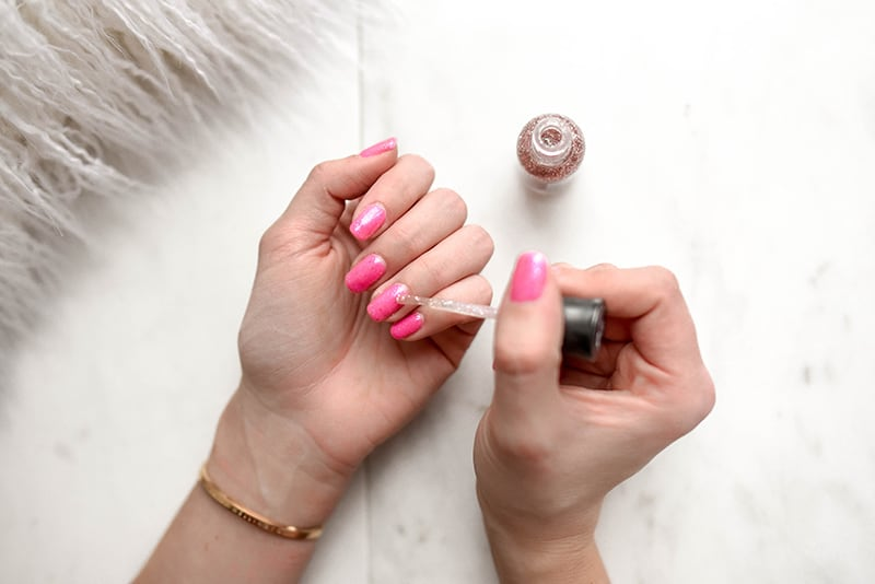 woman doing manicure with pink nail polish