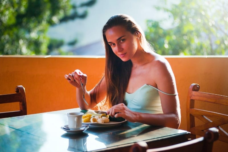 woman eating breakfast while sitting at table