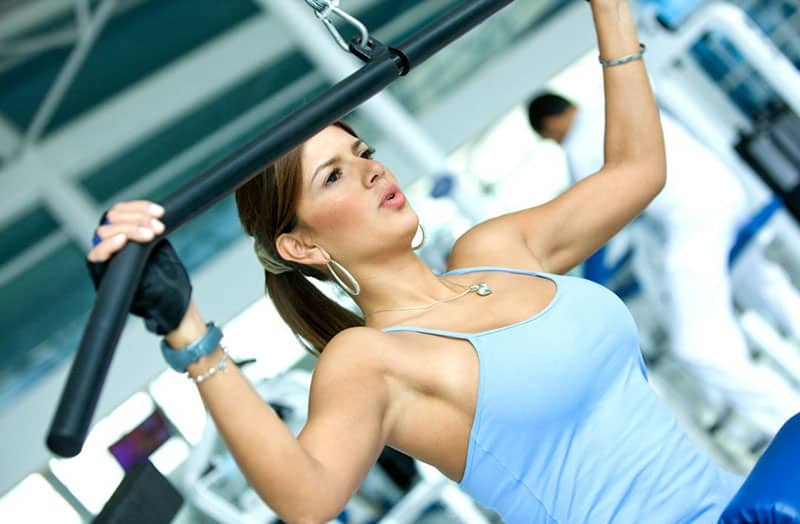 woman exercising inside the gym wearing light blue tank top