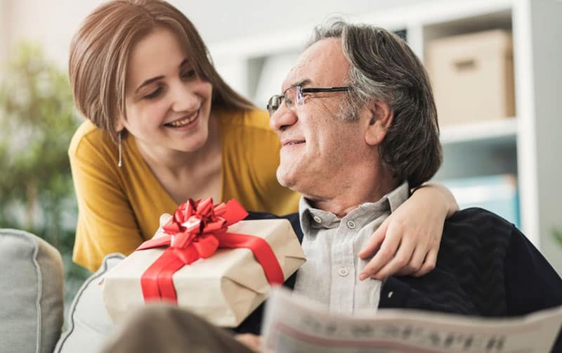 woman giving gift to an older man while sitting and reading a newspaper