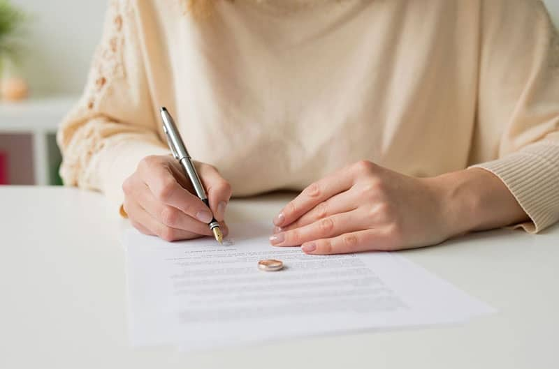 woman going thru divorce signing papers with ring on the paper