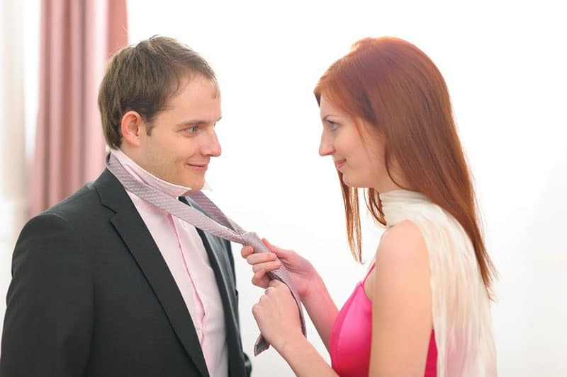 woman helping a man putting his neck tie while smiling