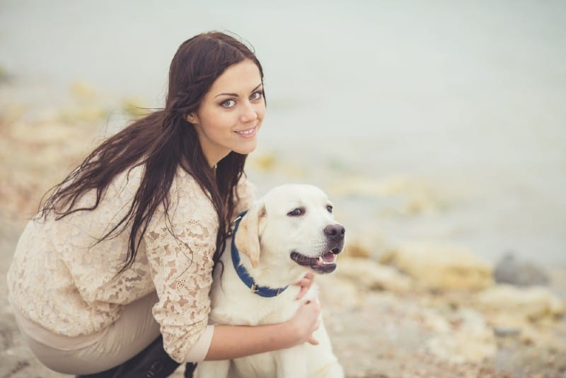 Young woman holding labrador dog