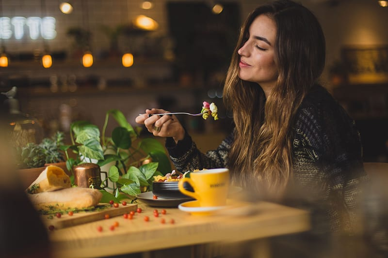 woman holding fork while eating diner