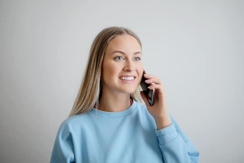smiling woman in blue sweatshirt holding phone