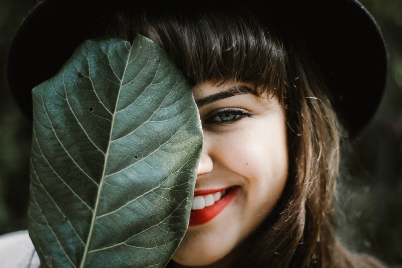 smiling woman with black hat holding leaf