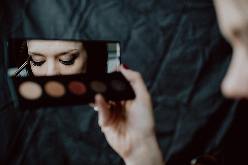 woman holding make up palette while applying eye shadow