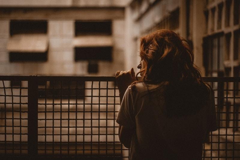 sad woman holding on railings during daytime
