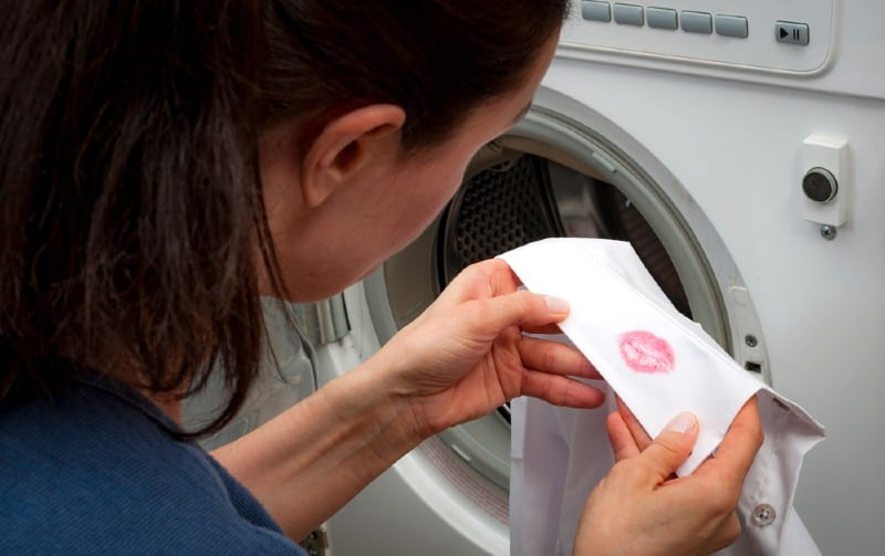Woman near washing machine holding white man shirt with red kiss lipstick marks