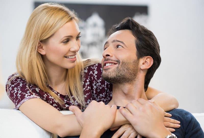 woman hugging a man sitting of sofa seeing eye to eye