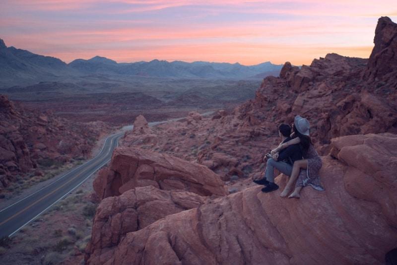 woman hugging man while sitting on rock during sunset