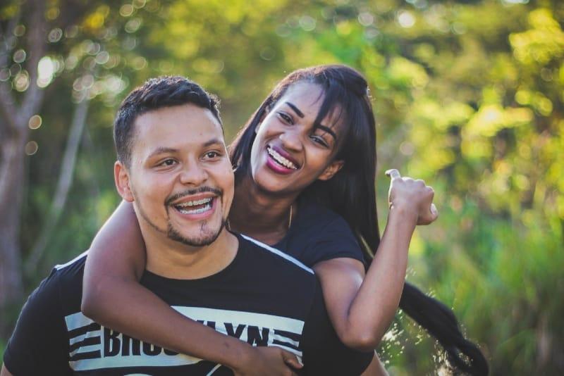 smiling woman hugging man in black t-shirt