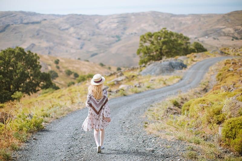 woman in a dress walking on a gravel road