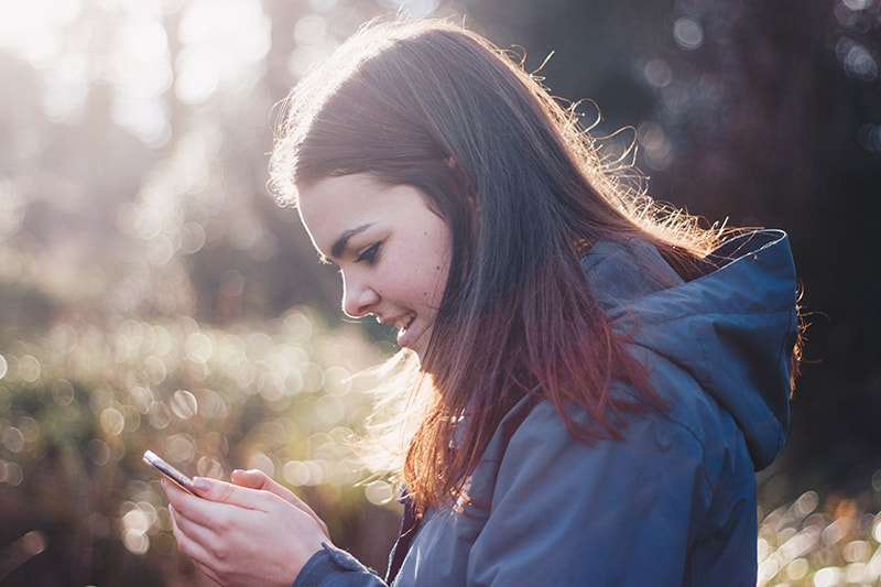 woman in blue hoodie smiling while using smartphone