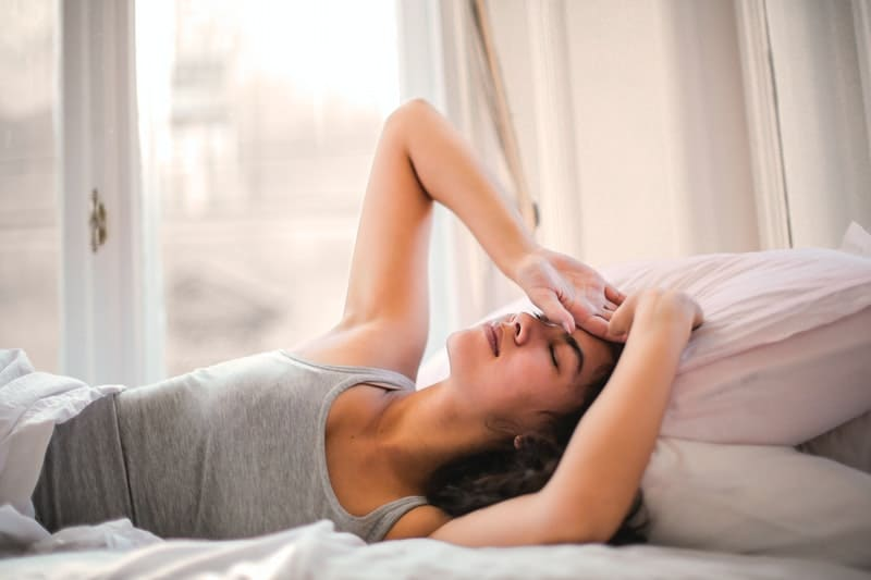 woman in gray tank top lying on bed with hand on her forehead