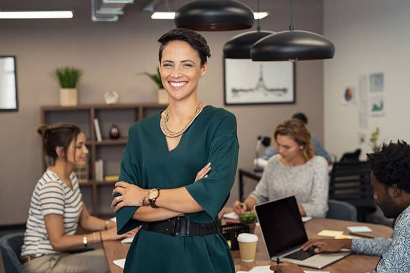 woman in green standing and smiling while 3 other people working on laptop at the back