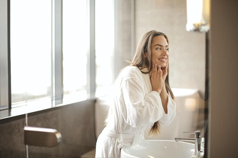 woman in white bathrobe touching her face in front of mirror