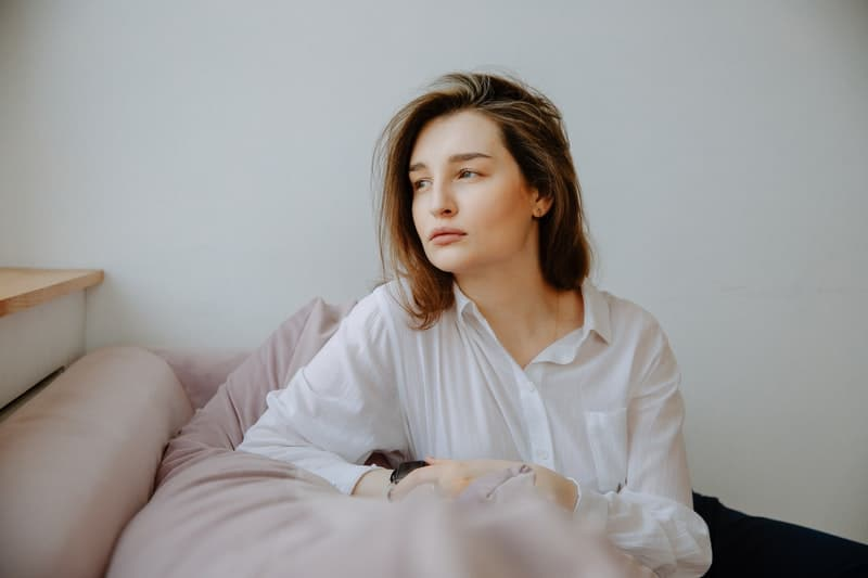 woman in white long sleeves sitting on a couch