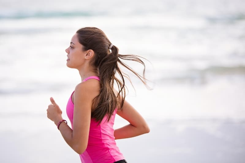 young woman in pink top jogging