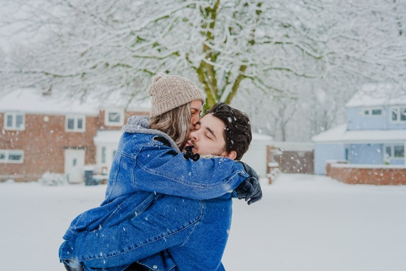 woman with cap kissing man on snow field