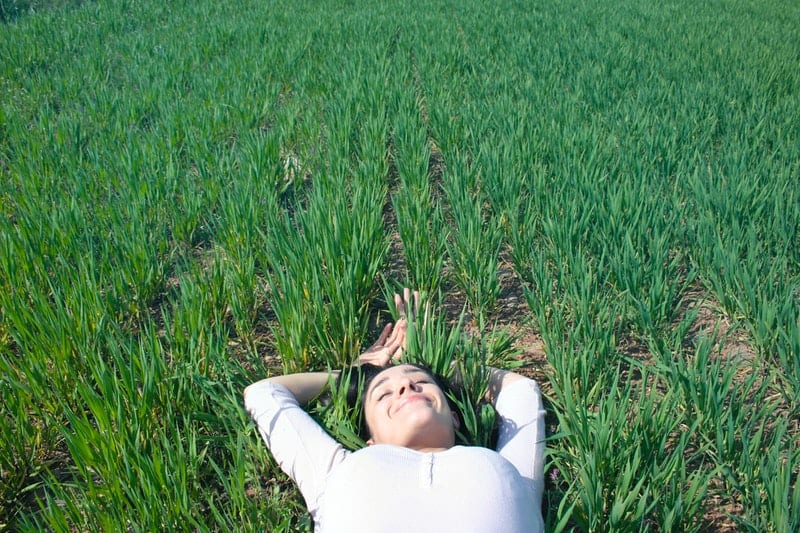 woman laying on field of green grass with hands above the head