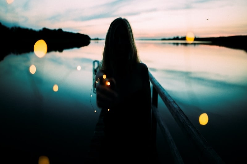 silhouette of woman leaning on metal railings