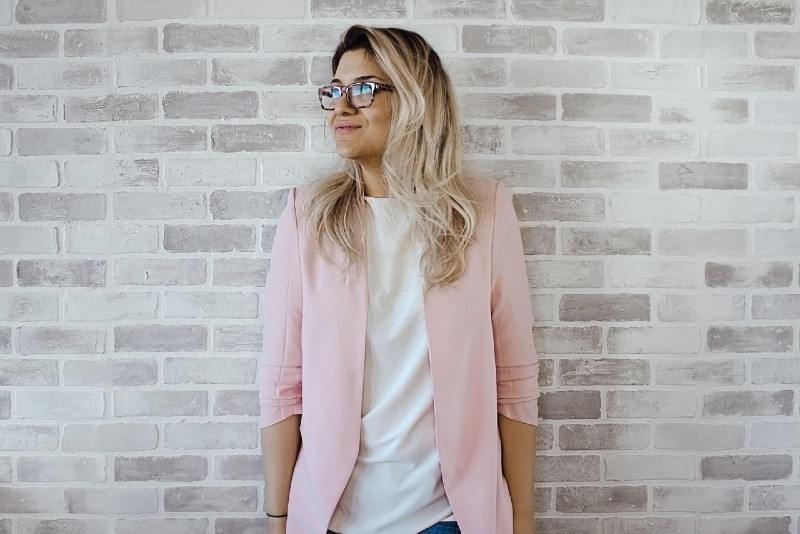 blonde woman with glasses leaning on wall