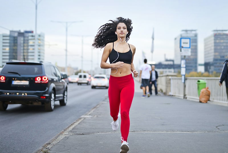 woman listening to music on earphones while running by the sidewalk