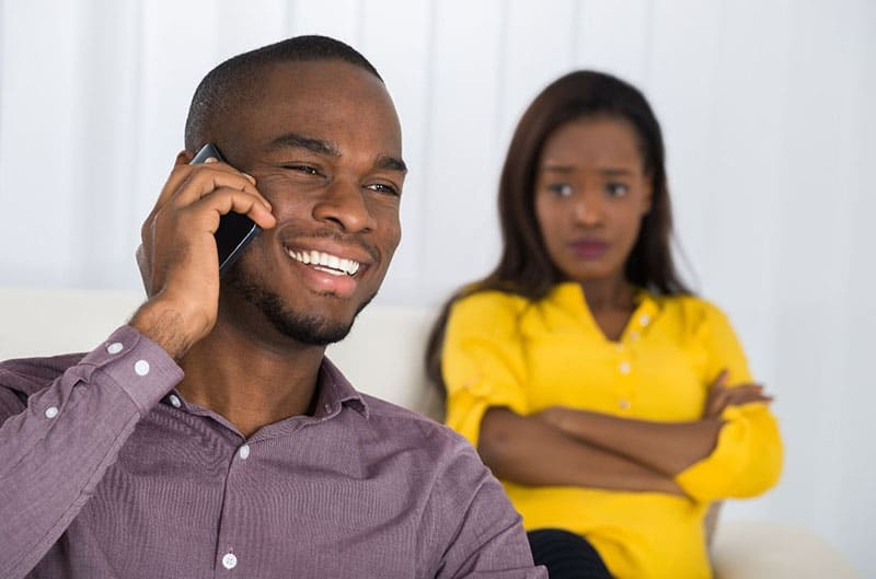 woman looking at a man making a call distant to her