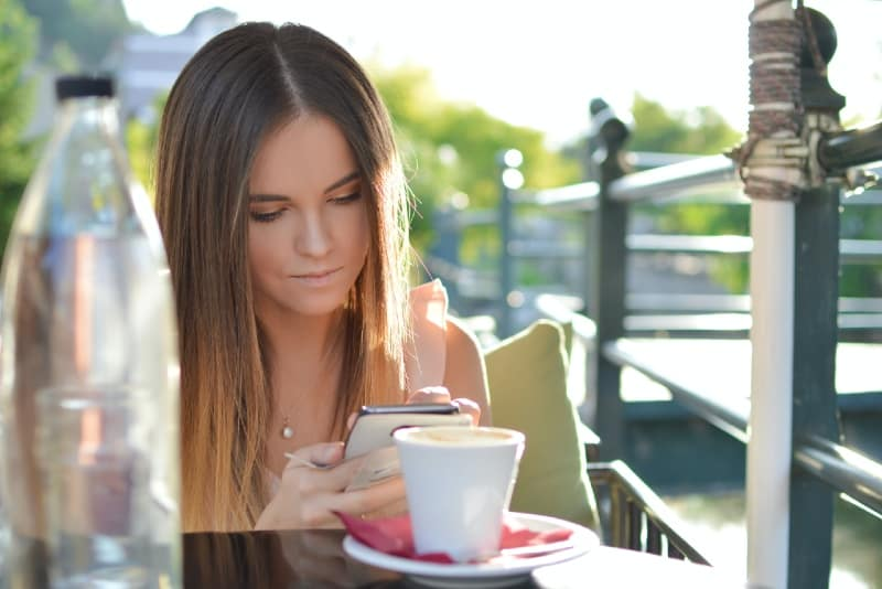 woman looking at phone while sitting at table in cafe